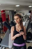 Mädchen mit dem Telefon, das für die Kamera aufwirft Lizenzfreie Stockfotos