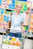 Mädchen mit dem Warenkorb voll vom Lebensmittel im Speicher Lizenzfreies Stockfoto