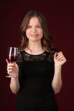 Mädchen mit dem Weinglas, das Gesichter macht Abschluss oben Dunkelroter Hintergrund Stockfotografie