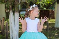 Mädchen mit den angehobenen Armen schaut beiseite, Kind mit einem Kranz von künstlichen Blumen auf ihrem Kopf Stockfotografie