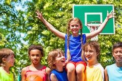 Mädchen mit den Armen oben auf Freunden schultert nach Spiel Stockbilder