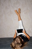 Mädchen mit den Beinen up und tablet in den Händen Lizenzfreie Stockbilder