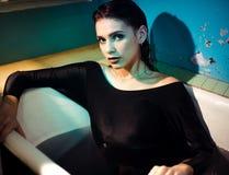 Mädchen mit den bloßen Schultern, die im Badezimmer mit farbigem purpurrotem Wasser liegen Art und Weisekonzept lizenzfreies stockfoto