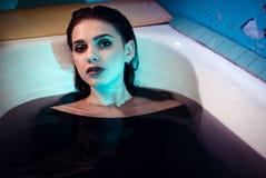 Mädchen mit den bloßen Schultern, die im Badezimmer mit farbigem purpurrotem Wasser liegen Art und Weisekonzept stockbild