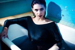 Mädchen mit den bloßen Schultern, die im Badezimmer mit farbigem purpurrotem Wasser liegen Art und Weisekonzept lizenzfreies stockbild