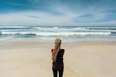 Mädchen mit den blonden Dreadlocks, die auf Ufer den Ozean aufpassend stehen Reise Stockfotografie