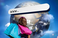 Mädchen mit den Einkaufstaschen, die Adresszeile mit großer Erde betrachten Stockbilder