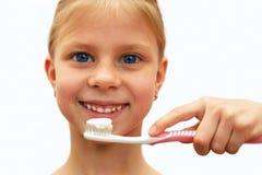 Mädchen mit den gesunden Zähnen, die eine Zahnbürste halten Stockbild