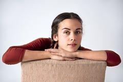 Mädchen mit den Händen gefaltet auf der Rückseite eines Stuhls Lizenzfreie Stockbilder