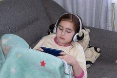 Mädchen mit den Kopfhörern, die im Telefon spielen lizenzfreie stockfotos