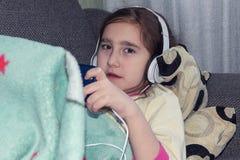 Mädchen mit den Kopfhörern, die im Telefon spielen lizenzfreie stockbilder