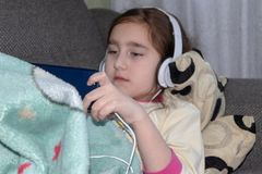 Mädchen mit den Kopfhörern, die im Telefon spielen stockbilder