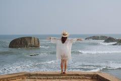 Mädchen mit den offenen Armen, die den Ozean betrachten stockfotografie