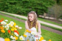 Mädchen mit den orange und gelben Mohnblumen Stockfotos
