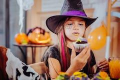 Mädchen mit den purpurroten und gelben Lippen, die Halloween tragen, entsprechen dem Essen des hellen kleinen Kuchens lizenzfreie stockfotos