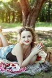 Mädchen mit den roten Lippen essen Erdbeere auf Picknick stockbild