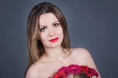 Mädchen mit den roten und purpurroten Blumen Stockbild