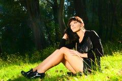 Mädchen mit den schönen Beinen, die auf grünem Gras aufwerfen Lizenzfreies Stockbild