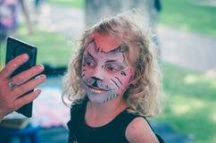 Mädchen mit der facepainting Katze Stockbild
