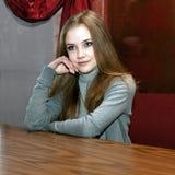 Mädchen mit der Hand auf Gesicht bei Tisch Stockfotos