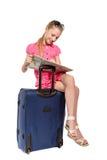 Mädchen mit der Karte, die auf einem Koffer sitzt Lizenzfreie Stockfotografie