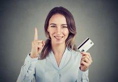 Mädchen mit der Kreditkarte, die Finger hochhält stockfotos