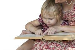 Mädchen mit der Mutter, die ein Buch auf weißem Hintergrund liest Stockbild