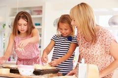 Mädchen mit der Mutter, die Käse auf Toast macht Lizenzfreie Stockbilder