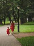 Mädchen mit der Mutter, die in Sommerpark geht stockbilder