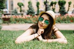 Mädchen mit der Sonnenbrille, die auf dem Gras am Sommertag im Stadtpark liegt lizenzfreies stockfoto
