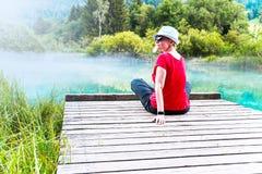 Mädchen mit der Sonnenbrille und weißem Hut, die auf einem hölzernen Pier sitzen und genießen stockbilder