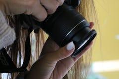 Mädchen mit der Spiegelreflexkamera, die ein Foto macht Stockfotografie