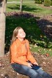 Mädchen mit der Tablette, die in der Sonne sich entspannt Stockfotografie