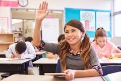 Mädchen mit der Tablette, die Hand in der grundlegenden Schulklasse anhebt stockbild