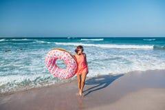 Mädchen mit Donut lilo auf dem Strand lizenzfreies stockbild