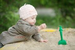 Mädchen mit Down-Syndrom, das im Sandkasten spielt Stockfotografie