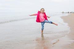 Mädchen mit drei Jährigen, das den Spaß gestanden auf einem Bein auf dem Strand hat Stockbild