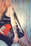 Mädchen mit E-Gitarre nahe Graffitiwand Nahaufnahme Stockfoto