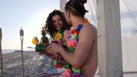 Mädchen mit einem alkoholischen Getränk, das zum Kerl am exotischen Erholungsort kommt, junge Paare des Sommerwochenendes in Hawa stock video