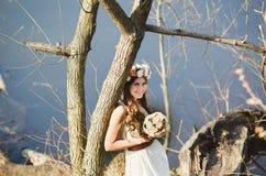 Mädchen mit einem Blumenkranz auf dem Kopf, der nahe Baum aufwirft Stockfoto