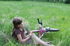 Mädchen mit einem Blumenstrauß im Gras lizenzfreie stockfotos