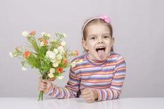 Mädchen mit einem Blumenstrauß von den Blumen, die bei Tisch sitzen Stockfotos