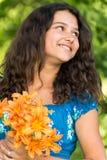 Mädchen mit einem Blumenstrauß von Lilien im Park Lizenzfreies Stockfoto