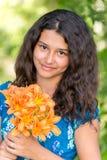 Mädchen mit einem Blumenstrauß von Lilien im Park Lizenzfreie Stockfotos