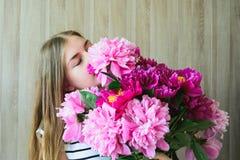 Mädchen mit einem Blumenstrauß von Pfingstrosen Stockbilder