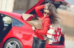 Mädchen mit einem Blumenstrauß von roten Rosen nahe dem Auto Stockbilder
