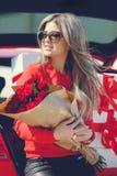 Mädchen mit einem Blumenstrauß von roten Rosen nahe dem Auto Lizenzfreie Stockfotos