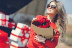 Mädchen mit einem Blumenstrauß von roten Rosen nahe dem Auto Stockfoto