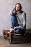 Mädchen mit einem Buch, das auf hölzernem Brett sitzt Grauer Hintergrund Lizenzfreies Stockfoto