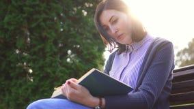 Mädchen mit einem Buch, das draußen auf der Bank bei Sonnenuntergang sitzt stock video